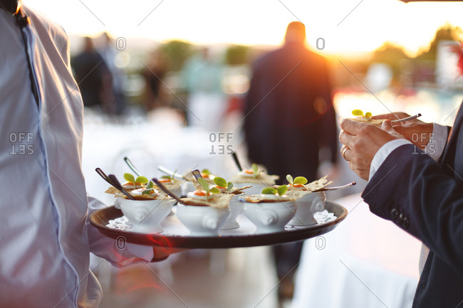 Waiter holding a serving tray with hors d'oeuvres in small dishes
