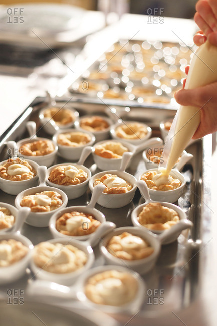 Chef piping cream onto pastry in individual serving bowls