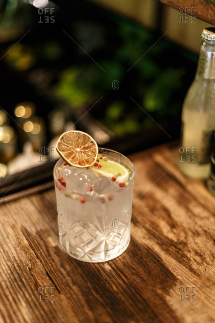 Cocktail in a serving glass with a citrus wedge, red peppercorns and herbs