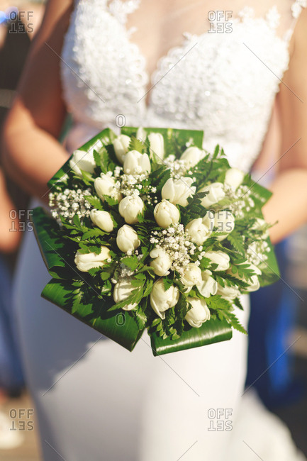 Bride holding a bouquet of white roses and baby's breath