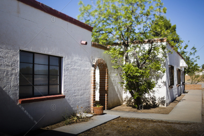 Outside of a white adobe house with a brick archway and windows
