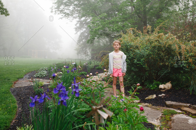 Little girl on a garden path on a foggy day