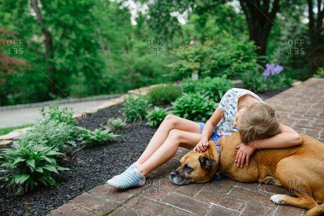 Girl lying on brick walkway with brown dog