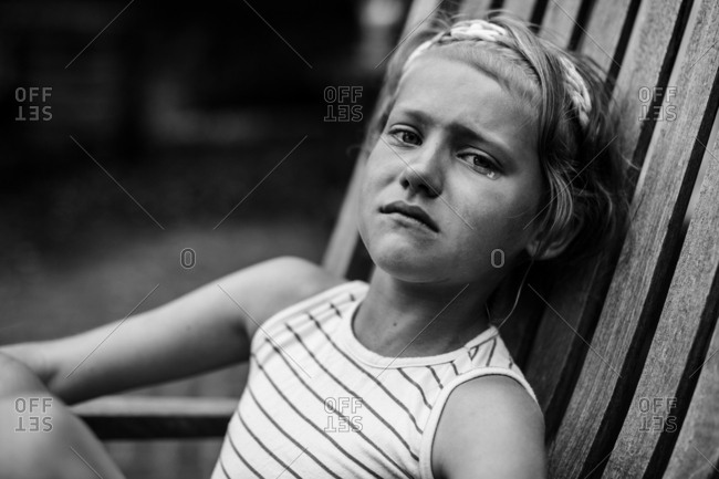 Little girl with tears in her eyes sitting on wooden chair