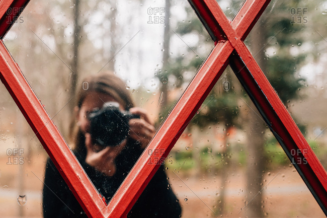 Photographer taking picture of reflective glass with raindrops