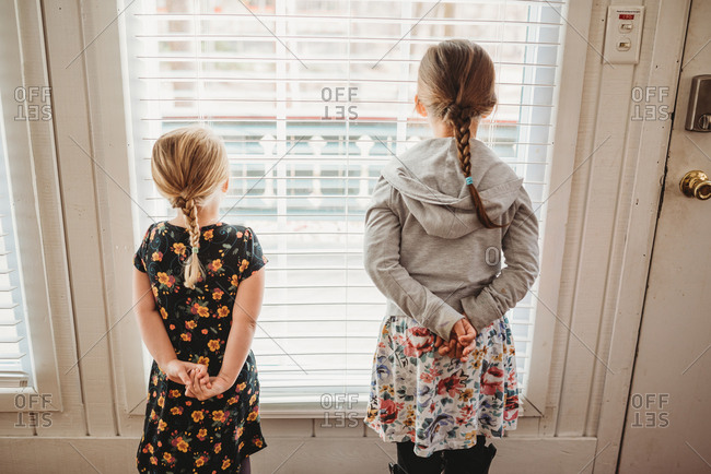 Two girls standing by window looking outside