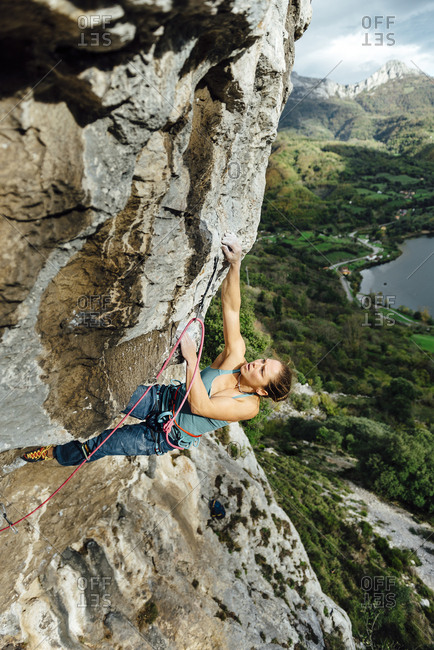 Young climber woman climbing on a overhanging limestone wall, Asturias, Spain