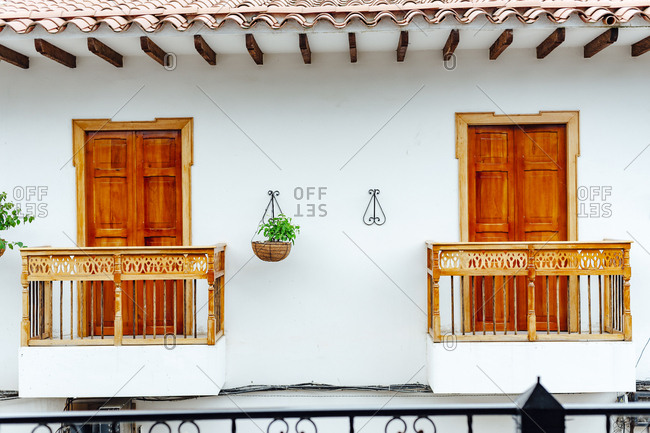 Two balconies in symmetry next to two hanging plants of the ceiling in Guatape, Colombia