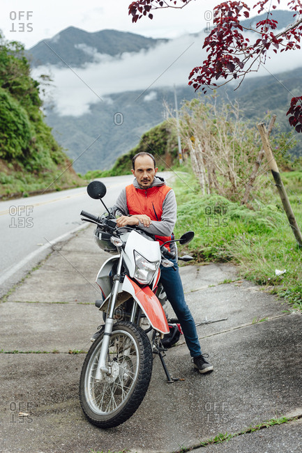 Midaged man posing with his motorbike in a mountain road in the countryside of Guatape, Colombia