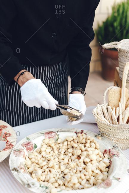 Detail of a waiter hands serving fried battered fish