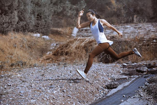 Woman running in rough terrain