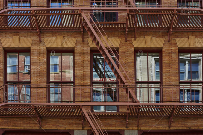 Facade of brownstone with fire escapes in Manhattan, New York, USA