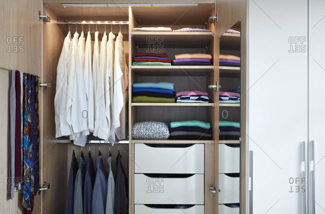 Interior view of wardrobe with drawers, clothes on hangers and shelves,