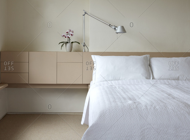 Interior view of a modern carpeted bedroom with double bed and shelving unit