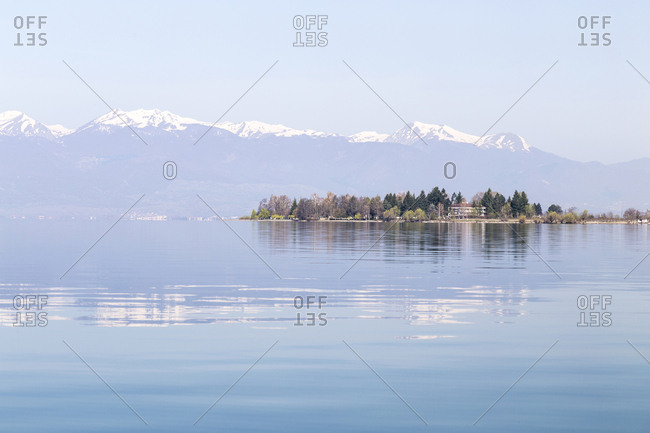 A small hotel on an isolated peninsula in Lake Ohrid, in Macedonia, with snow-capped Albanian mountains beyond