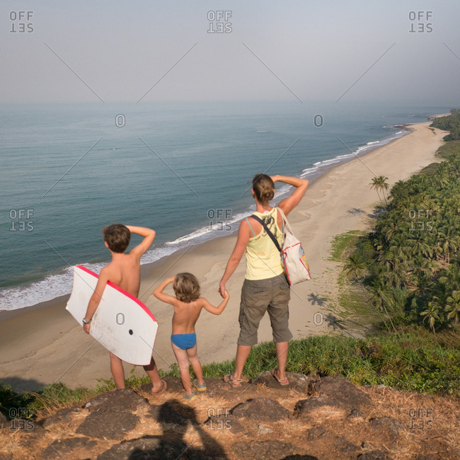 A European mother and two sons scan the horizon for a new adventure on a beach in India