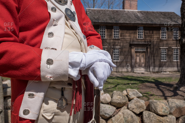 A historical reenactor stands in front of a historic house on the Minuteman Trail