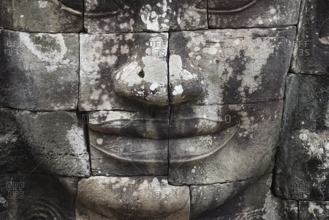 Close up of a stone face on a tower of Angkor Thom