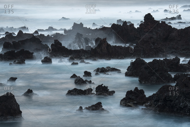 A long exposure of surf pouring over lava rocks at Easter Island