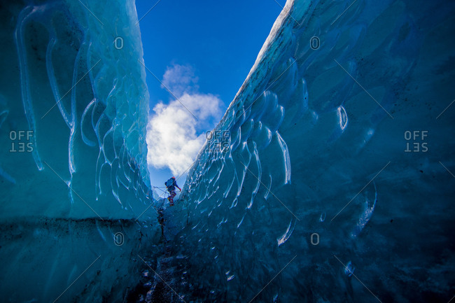 A woman walks through a crevasse in the Vatnajokull glacier