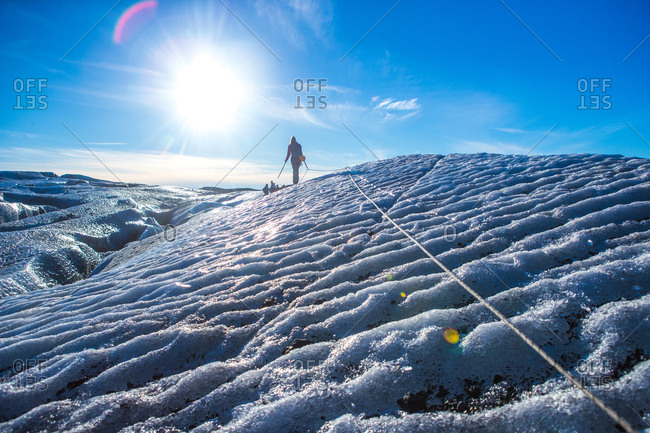A woman walks along a safety rope to keep from sliding into a crevasse on the Vatnajokull Glacier