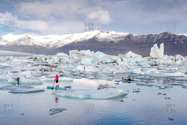 A woman on an inflatable paddleboard paddling on the Jokulsarlon glacier lagoon