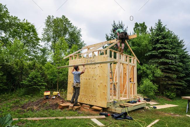 Two men building a chicken coop building