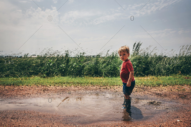 Toddler boy standing in mud puddle