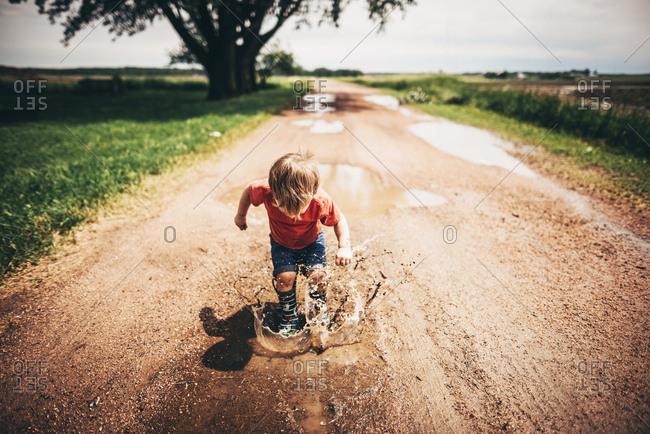 Toddler boy making a splash in mud puddles
