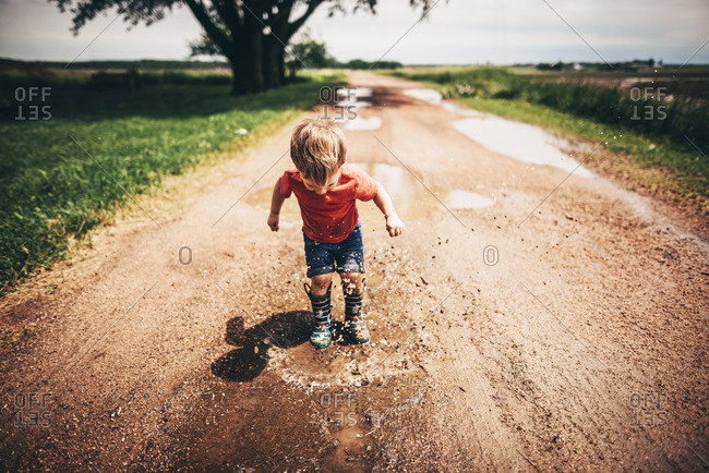 Toddler boy jumping in mud puddles