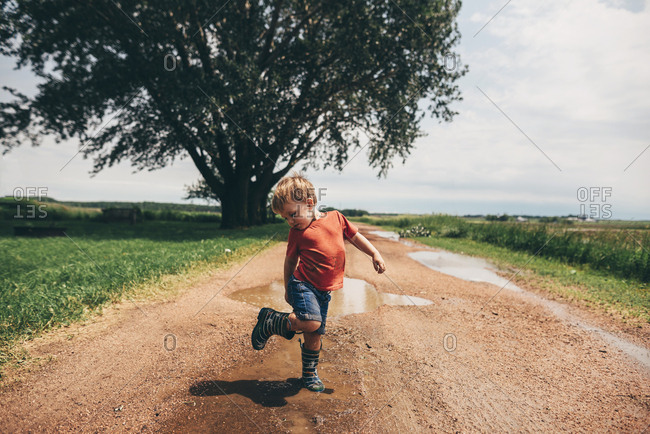 Toddler boy checking out boot in mud puddles