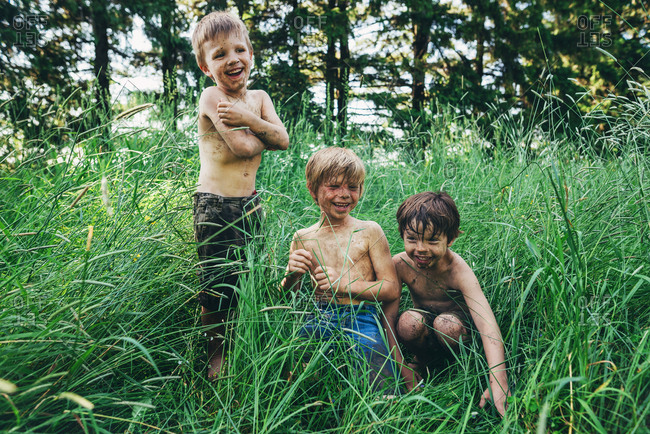 Three young boys covered in dirt playing in tall grass in the summer