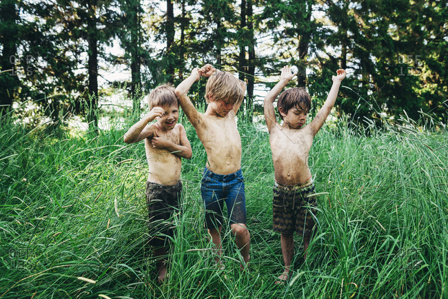 Three messy boys standing in tall grass in the summer