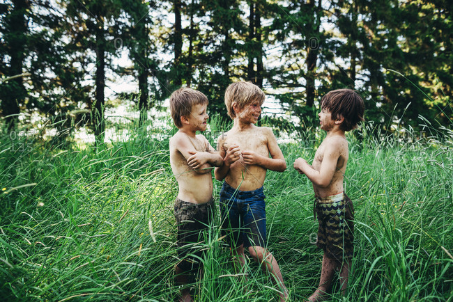 Three young boys covered in dirt hanging out in tall grass in the summer