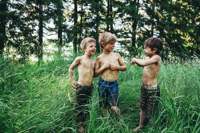 Three young boys covered in dirt in tall grass in the summer