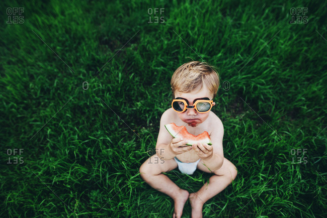 Young toddler wearing goggles and eating watermelon wearing a diaper