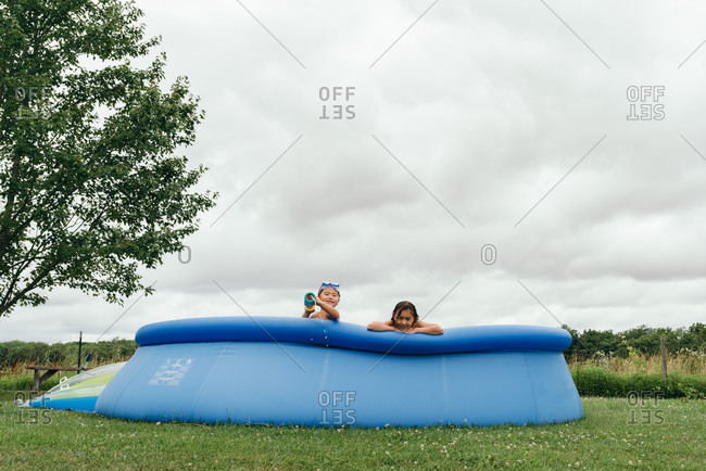 Children playing with water gun in above ground swimming pool
