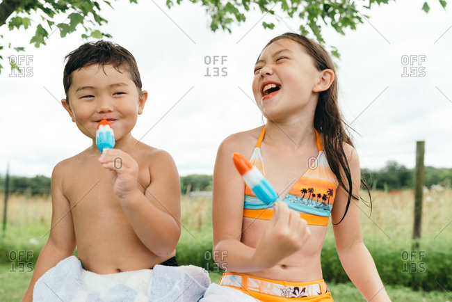 Laughing girl sitting next to brother eating red, white, and blue ice pop