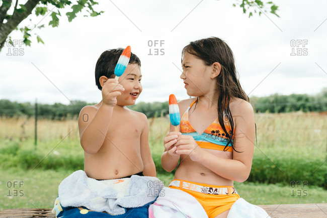 Girl looking at her brother's messy face after eating an ice pop