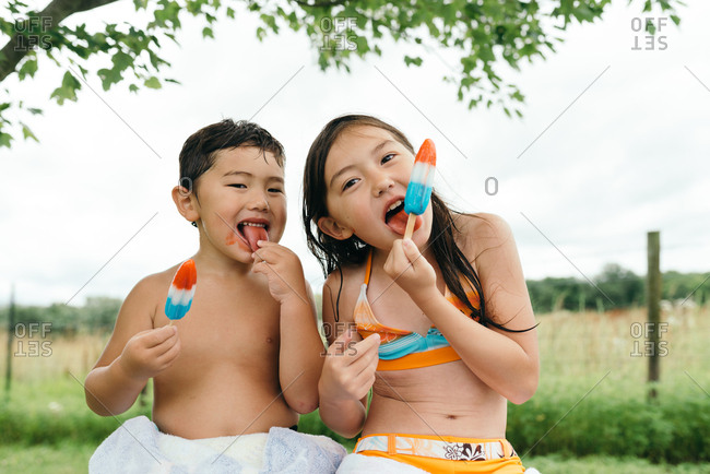 Sister and brother sitting together eating red, white, and blue ice pops