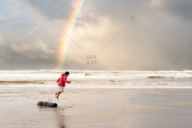Boy on a beach near a rainbow