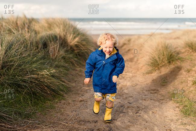 Laughing boy on beach path