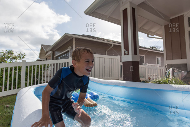 Boy in wetsuit in backyard pool