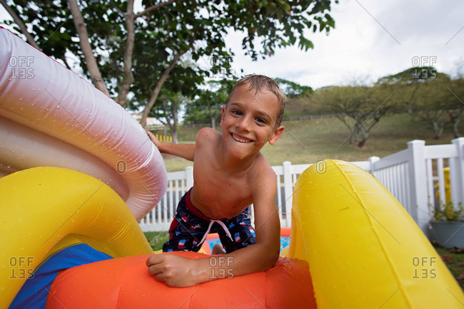 Boy on inflatable waterslide