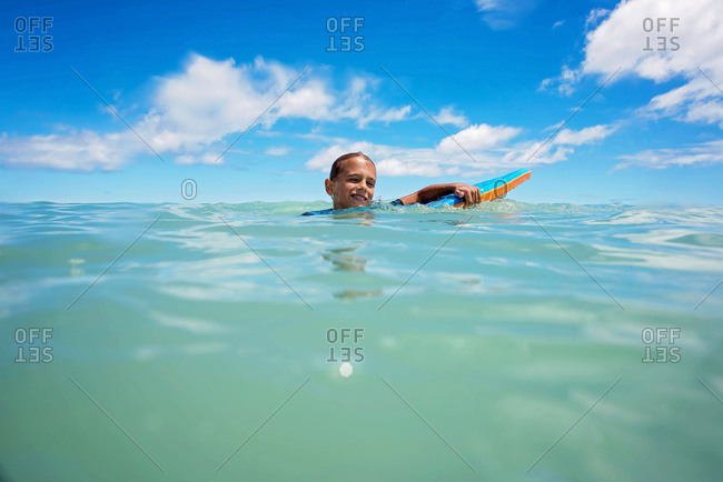 Boy smiling with board in sea