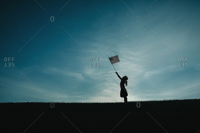 Girl silhouetted holding American flag