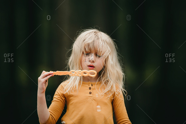 Blonde girl blowing bubbles