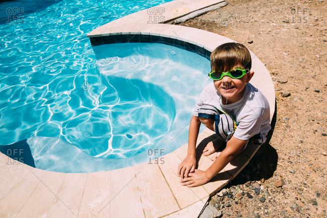 Boy sitting on side of swimming pool
