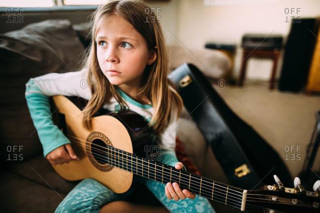 Little girl practicing guitar