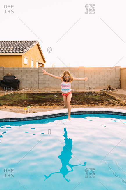 Little girl jumping into a swimming pool